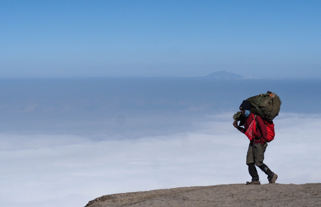 A porter atop Kilimanjaro's Baranco Wall, with Mt. Meru emerging from a sea clouds behind him