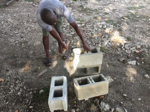 Our incredible grounds keeper, Jean Claude, helps me prepare blocks to make a rocket stove that burns fuel more efficiently